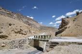 Metall construction bridge across river in mountains — Stock Photo