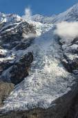 Glacier flowing from high snow maountains — Stock Photo