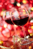 Red wine in wineglasses  against holiday lights background. — Stock Photo