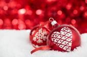 Bombki choinkowe z sercem malowane i śnieżynka przeciwko czerwony hol — Zdjęcie stockowe