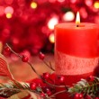 Christmas decoration with candle against red holiday lights. — Stock Photo #56068791