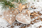 Wooden hearts on snow-covered wooden background. — Stock Photo