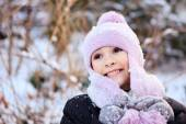 Cheerful beautiful girl in purple winter hat in the snow under the Christmas tree — Stock Photo