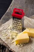 Grated cheese and metal grater — Stock Photo