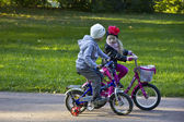 Children ride bicycles in the Lomonosov Park, September 2014 — Stock Photo