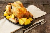 Chicken baked with potatoes on a cast iron pan on a wooden backg — Stock Photo