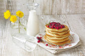 Pancake with lingonberry jam and a milk bottle — Stock Photo