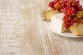 Cheese and fresh grapes on a wooden background — Foto Stock