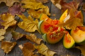 Pumpkin, cut into pieces on a wooden background strewn with autu — Stock Photo