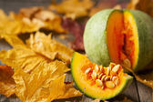 Green pumpkin and pumpkin slice on wooden background strewn wit — Stock Photo