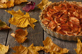 Apple pie with cinnamon on the table strewn with autumn leaves — Stock Photo
