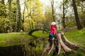 Adorable little girl hiking in the forest, sitting on a stump — Stock Photo