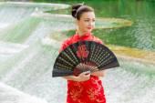Joven chica caminando en traje nacional con un ventilador cerca de la r — Foto de Stock