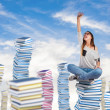Young woman sitting on books tower — Stock Photo #62737109