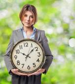Young businesswoman holding clock — Photo