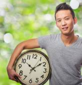Young asian man holding clock — Photo