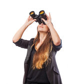 Young woman looking through binoculars — Stock Photo