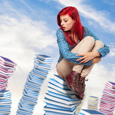 Young woman sitting on books pile — Foto de Stock