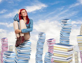 Young woman sitting on books pile — Stock Photo
