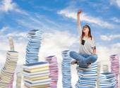 Young woman sitting on books tower — Stock Photo