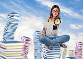 Young woman sitting on books tower — Fotografia Stock