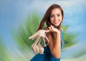 Young cute woman holding shoes — Stock Photo