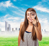 Girl looking through magnifying glass — Stock Photo
