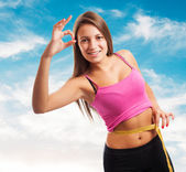 Sporty young girl measuring weight — Stock Photo