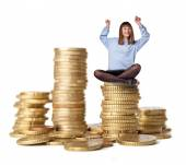 Young woman winner on coins tower — Stock Photo