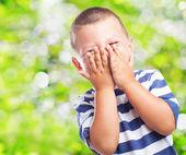 Fun kid hiding his face — Stock Photo