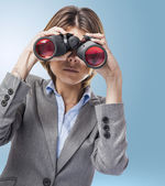 Young woman looking through binoculars — Stock Photo