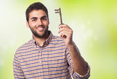 Young man holding old key — Stockfoto