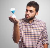 Young man holding sand timer — Stock Photo