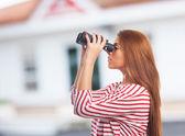 Woman looking throught a binoculars — Stok fotoğraf
