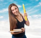 Studerande som innehar en stor penna och böcker — Stockfoto