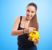 Woman inserting coin in a piggy bank — Stock Photo