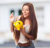 Girl inserting coin in a piggybank — Stock Photo
