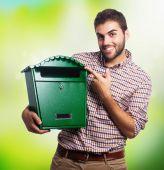 Junger Mann hält eine malbox — Stockfoto
