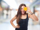Woman holding an orange slice joking — Stock Photo