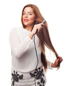 Woman using her hair irons — Stock Photo