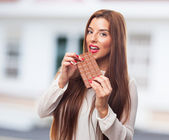 Pretty girl biting a chocolate bar — Stock Photo