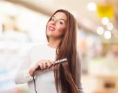 Woman using hair irons — Stock Photo