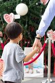 Child holding his mum hand and christmas tree — Stock Photo