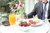 Businessman using mobile phone during breakfast — Stock Photo