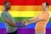 Homosexual couple with a rainbow gay pride flag — Stock Photo