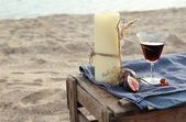 Candle and red wine on the beach — Stock Photo