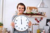 Happy young woman showing clock in christmas decorated kitchen — Stock Photo