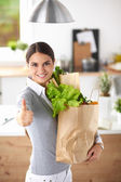Young woman holding grocery shopping bag with vegetables and showing ok — 图库照片