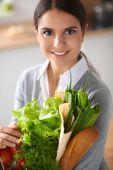 Giovane donna holding grocery shopping bag con verdure in piedi in cucina. — Foto Stock