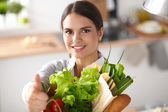 Young woman holding grocery shopping bag with vegetables and showing ok — Foto de Stock